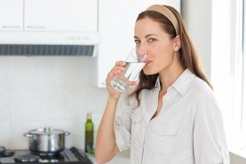 Ragazza beve un bicchiere d'acqua per rassodare la pelle