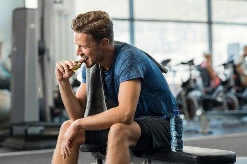 Uomo che mangia una barretta in palestra