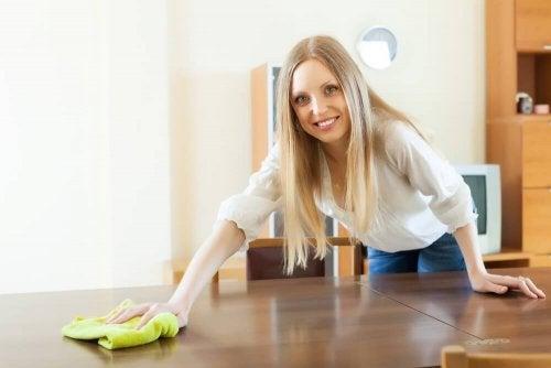 Donna pulisce il tavolo con un panno