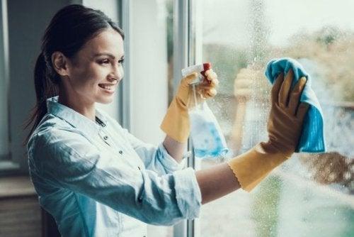 Donna che usa un detergente per vetri