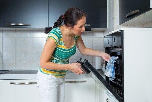 Donna toglie una teglia dal forno