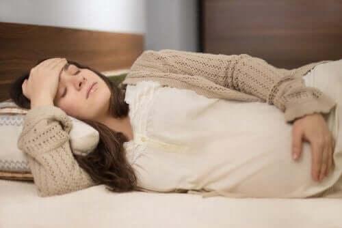 Donna incinta affaticata e sdraiata sul letto