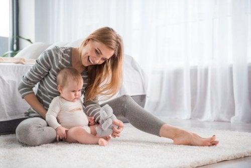 Mamma cerca di stimolare il bambino a gattonare