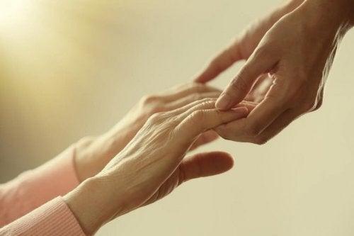 Mani di persona giovane toccano mani di donna anziana