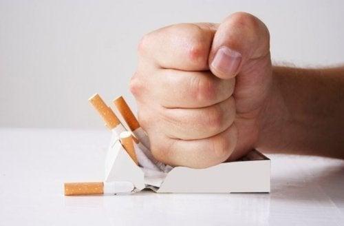 Pugno schiaccia un pacchetto di sigarette