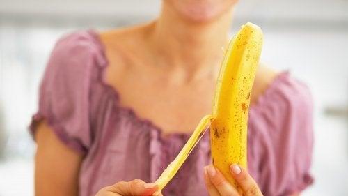 Ragazza sbuccia una banana