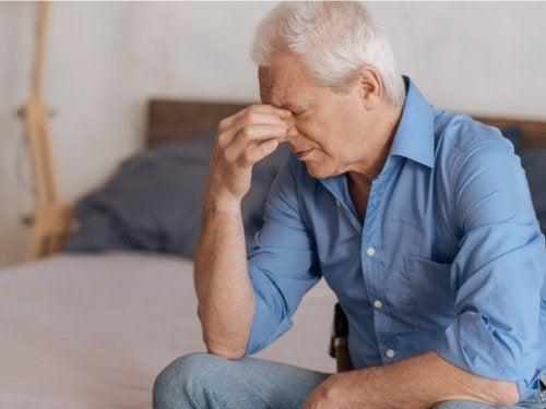 Uomo anziano triste con la mano sugli occhi