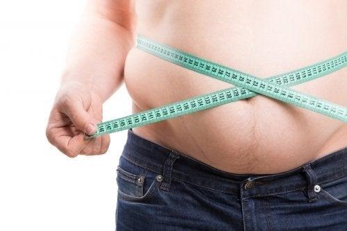 Uomo misura la circonferenza addominale con il centimetro
