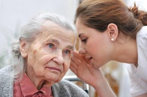 Donna giovane parla all'orecchio di una donna anziana