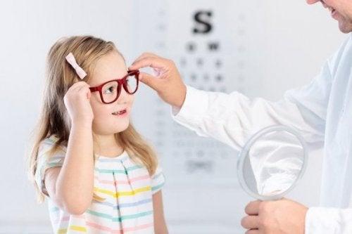 Bambina con gli occhiali disturbi della vista nei bambini