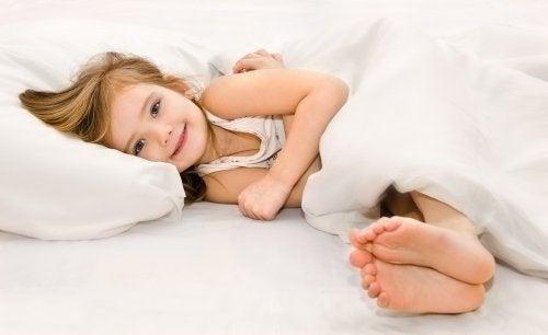 Bambina sorridente nel letto