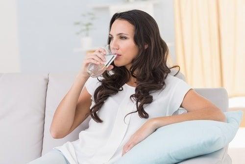 Donna che beve l'acqua per prevenire la cistite dopo i rapporti