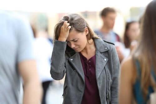 Ragazza con mano alla testa in mezzo alla folla per evitare le ossessioni mentali