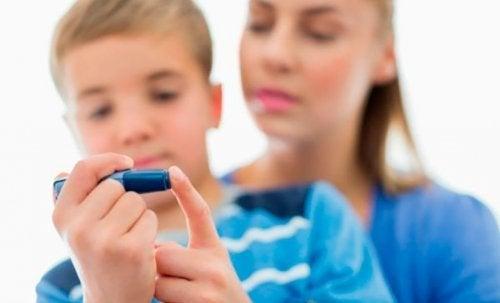 Madre e figlio con penna per la misurazione della glicemia
