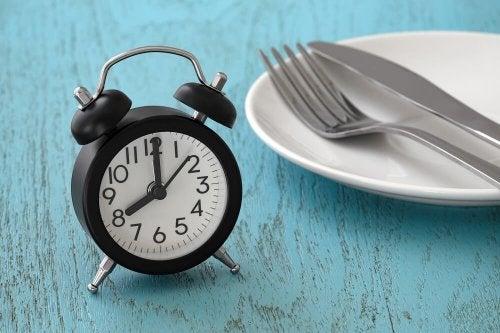 Benefici del digiuno intermittente: piatto, forchetta e sveglia