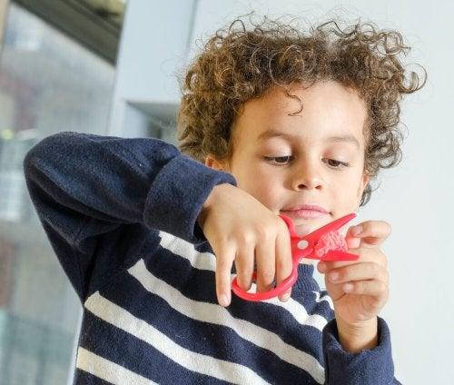 Bambino che gioca con le forbici e la cera