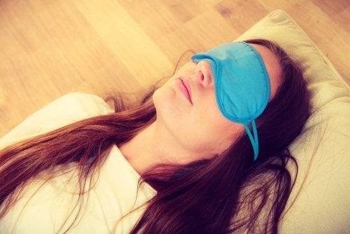 Ragazza con mascherina sugli occhi per dormire meglio