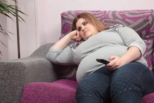 Donna obesa seduta sul divano