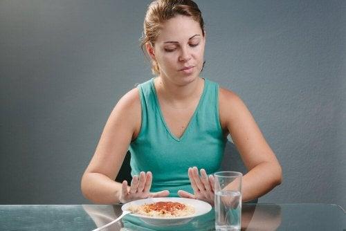 Donna che rifiuta un piatto di pasta