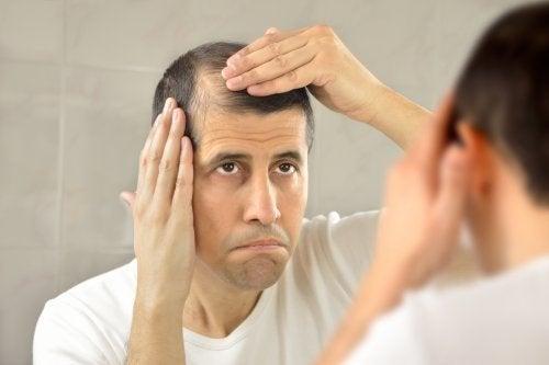 Uomo si controlla i capelli allo specchio