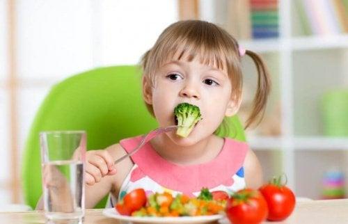 Bambina che mangia un broccolo