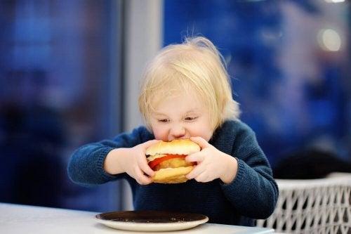 Bambino che addenta un hamburger