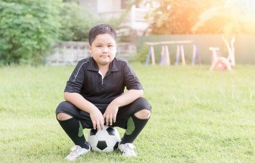 Bambino che fa calcio per combattere la obesità infantile