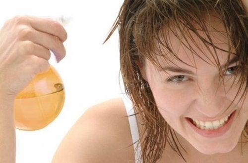 Donna applica una lozione sui capelli