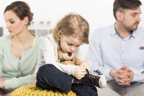 Bambino che si allaccia le scarpe e genitori distratti