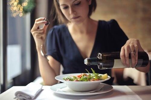 Donna condisce piatto di insalata