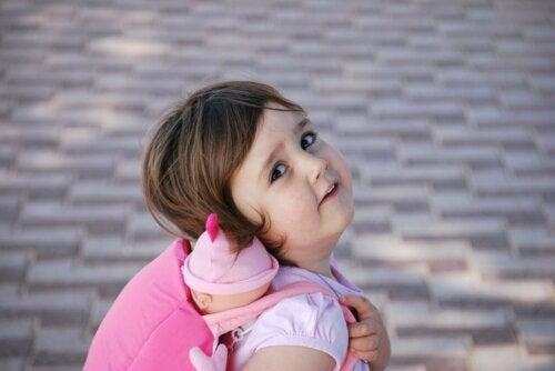 Bambina con bambola nello zainetto