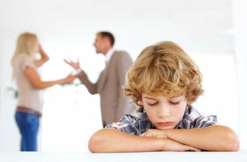 Bambino triste e genitori che discutono