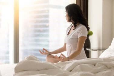Ragazza che fa yoga sul letto