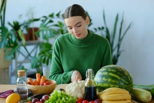 Ragazza a tavola con frutta e verdura