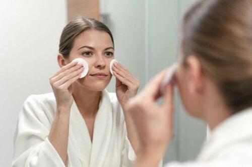 Ragazza di deterge il viso allo specchio