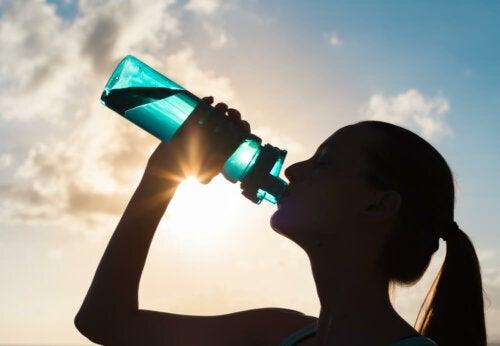 Donna che beve per reintegrare gli elettroliti nel corpo