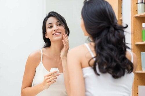 Donna che applica una crema sul viso