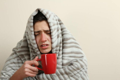 Ragazzo raffreddato con coperta e tisana