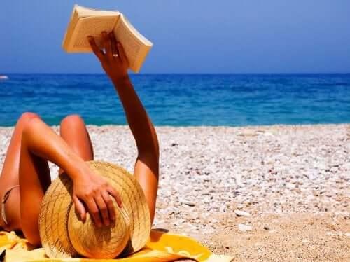 Donna in spiaggia che legge un libro