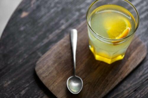 Bicchiere con acqua e limone e cucchiaino