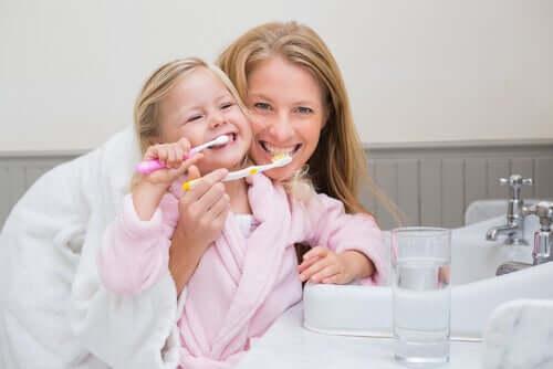 Mamma e figlia che si lavano i denti