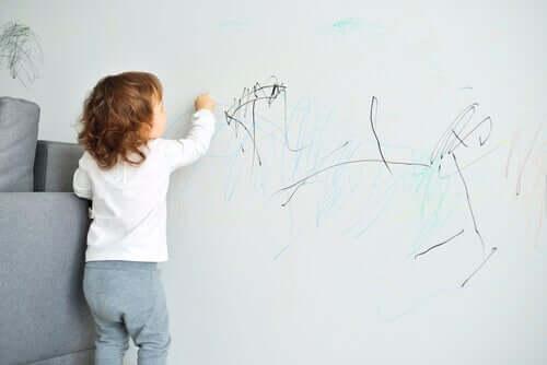 Bambino che scarabocchia la parete di casa