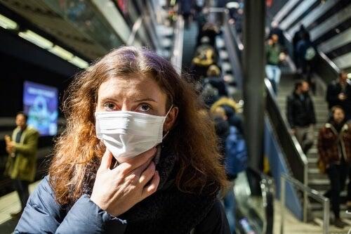 Donna con mascherina e differenza tra influenza, coronavirus e allergia