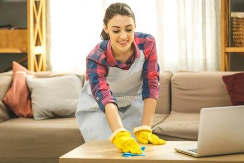 Pulizia e disinfezione in casa, donna passa la spugna sul tavolo