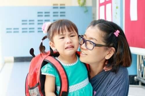 Primo giorno nella nuova scuola, mamma e figlia che piange