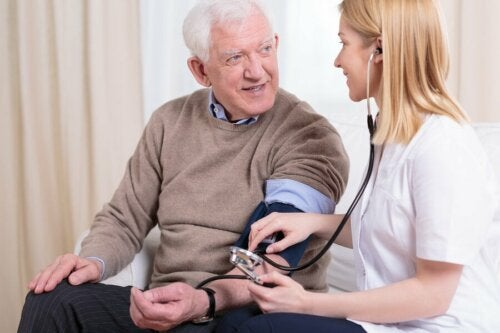 Dottoressa misura la pressione a paziente anziano