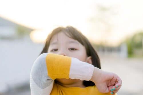 Bambina che tossisce nella piega del gomito