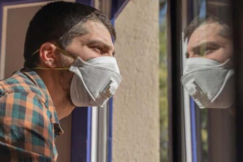 Uomo con la mascherina che guarda dalla finestra