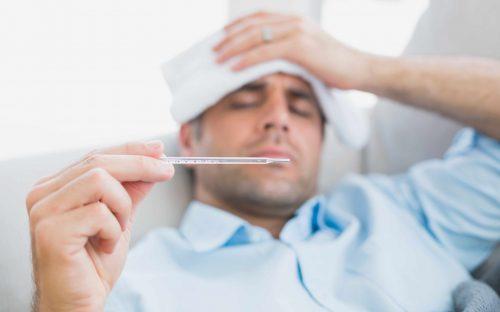 Uomo con la febbre e termometro