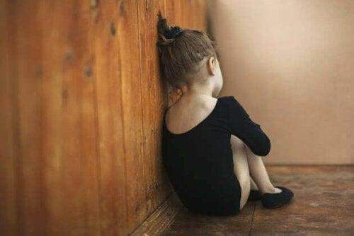 Autismo, bambina seduta in un angolo